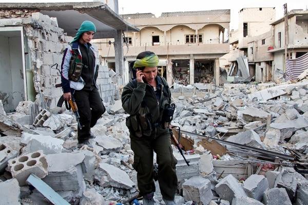 Combatientes kurdas sirias en medio de los escombros producto de los enfrentamientos contra el Estado Islámico en la ciudad de Kobane, de donde las fuerzas de defensa lograron expulsar a los yihadistas. | EFE