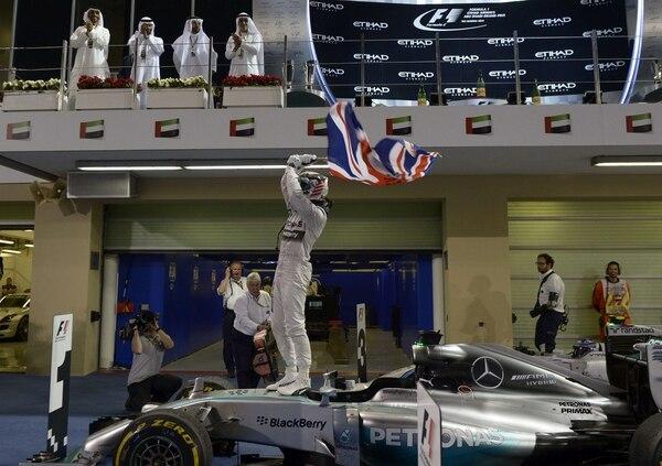 Lewis Hamilton ondea la bandera de Gran Bretaña tras vencer en Abu Dabi y confirmarse campeón de Fórmula 1.