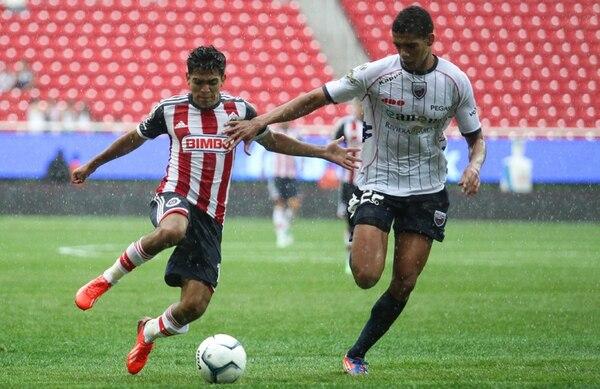 Jesús Sánchez (izq.), de Chivas, marcado por Carlos Calvo de Atlante, ayer en el estadio Omnilife. | EFE