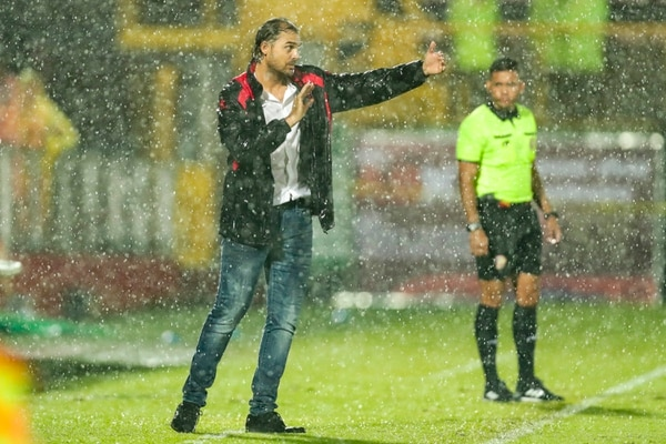 Andrés Carevic da indicaciones a sus jugadores en medio de un aguacero en el Morera Soto, en Alajuela. Fotografía José Cordero