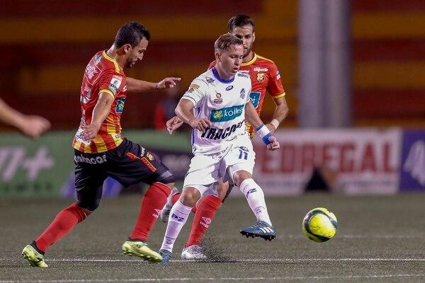 Anthony López conduce la pelota, mientras es presionado por Rándall Azofeifa. Fotografía: José Cordero.