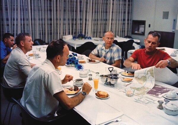 """Los astronautas Neil Armstrong, Buzz Aldrin y Michael Collins desayunan con su jefe Donald """"Deke"""" Slayton (camisa roja), el día en el que la misión salió al espacio. Fotografía: Archivo NASA"""