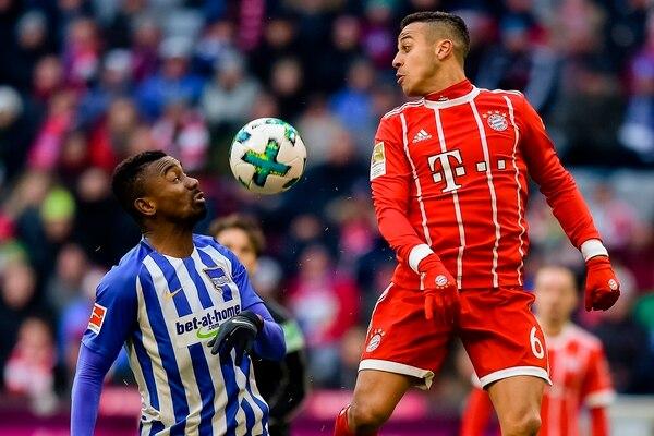 Salomon Kalou (izq.) del Hertha, disputa la pelota con el jugador del Bayern Múnich, Thiago Alcantara. Foto: AFP / Guenter Schiffmann