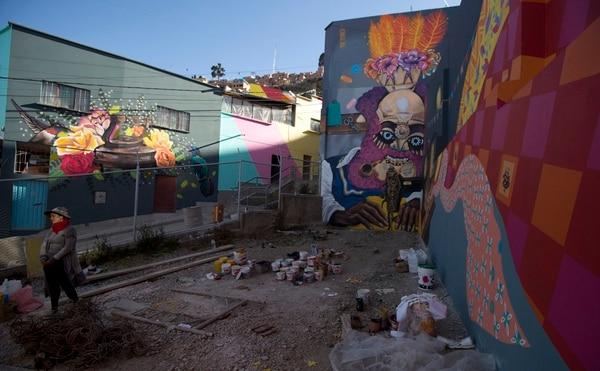 La artista urbana Knorke Leaf camina cerca de su mural que hace referencia al Baile de la Morenada, una danza folclórica declarada Patrimonio Cultural de Bolivia, desde el 2001. Foto: AP/Juan Karita.