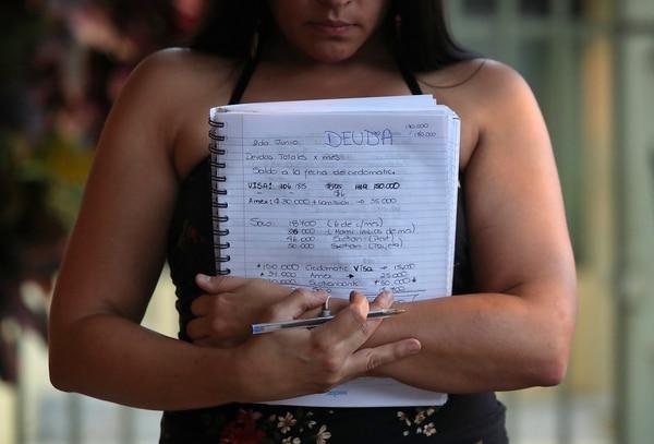 Natalia Solano muestra el cuaderno donde lleva cuentas. De su salario de ¢900.000, le quedan libres unos ¢50.000 por mes. /Fotografía: John Durán