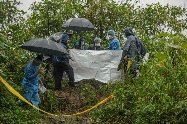 Bajo la lluvia, los forenses recogieron el cuerpo y los indicios que pudieran ayudar al OIJ a dar con los responsables.