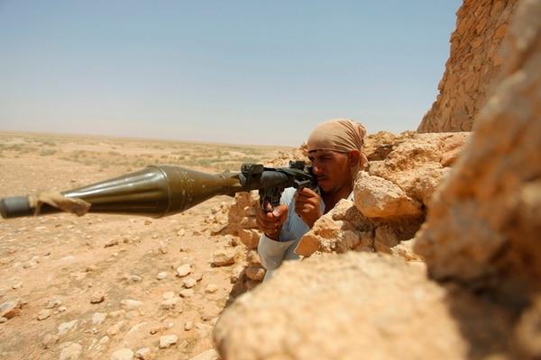 La foto superior muestra a un combatiente chiita vigilando en Najaf, el sur de Bagdad. Abajo, izquierda, un voluntario del Ejército iraquí se entrena en la ciudad de Najaf. Abajo, derecha, niños iraquíes refugiados en Khazer. | AP
