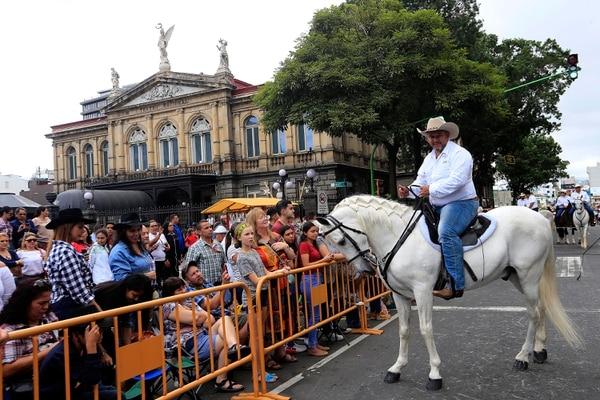 Cientos de personas se ubicaron a la orilla de la carretera para ver a los cabalistas hacer el tradicional recorrido en una tarde más nublada que de costumbre. Mario Granados y su caballo Humo, frente al Teatro Nacional. Foto: Rafael Pacheco
