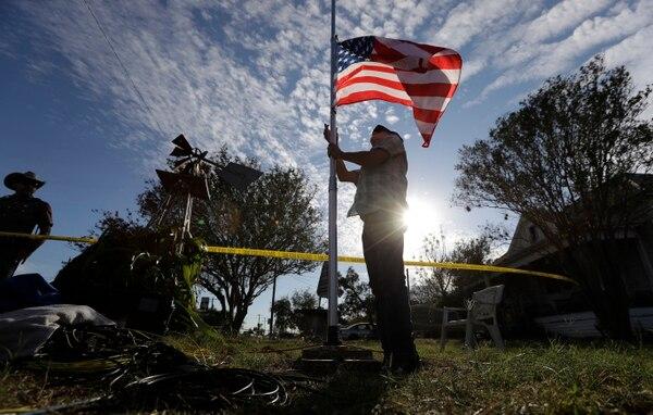 Un agente policial colocaba la bandera estadounidense a media asta, el lunes 6 de noviembre del 2017, cerca de la iglesia bautista de Sutherland Springs, Texas, donde ocurrió la matanza.