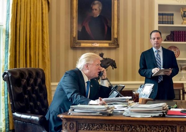 El presidente Donald Trump mientras conversaba este sábado con su homólogo de Rusia, Vladimir Putin, desde la Oficina Oval de la Casa Blanca. Testigo fue el jefe de gabinete, Reince Priebus.