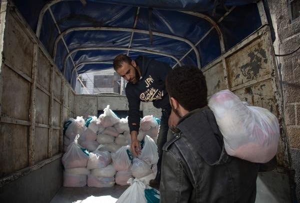 Familias sirias reciben ayuda de la Fundación Humanitaria Al-Sham en el barrio de Al-Marjah, en la ciudad de Alepo.