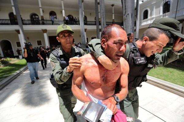 Un supuesto partidario del Gobierno que formaba parte de un grupo que trató de forzar su entrada en la Asamblea Nacional, fue detenido temporalmente por guardias nacionales, en Caracas