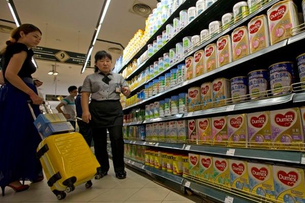 Una vendedora en un supermercado de Pekín promovía ayer los productos lácteos de una marca contaminada, pese a la alerta hecha por Fonterra. | AP.