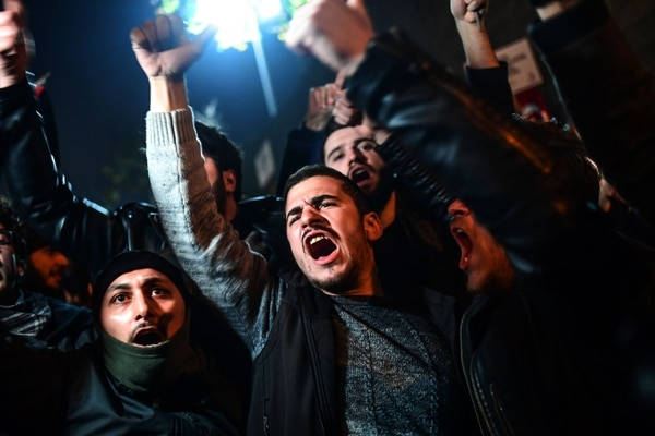 Protesters chant slogans during a demonstration against the US and Israel in front of the US consulate in Istanbul on December 6, 2017. Hundreds of people staged a protest outside the US consulate in Istanbul angrily denouncing the US president's move to recognise Jerusalem as the capital of Israel. Around 1,500 people gathered outside the well-protected compound close to the Bosphorus which was sealed off by police with barricades, an AFP correspondent said. / AFP PHOTO / OZAN KOSE
