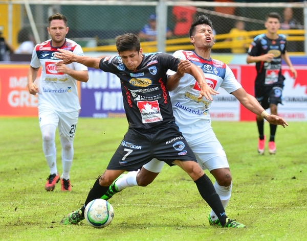 El griego Alberth Villalobos intenta cubrir el balón ante la marca del brumoso José Leiva, en la fecha 11 del Torneo de Apertura.