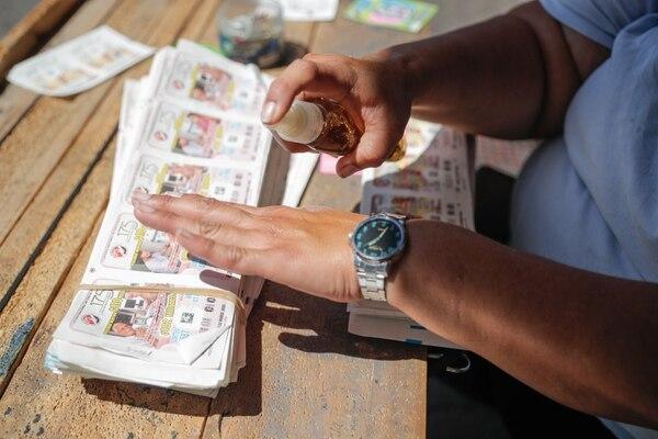 Kimberly Montoya es vendedora de lotería en San José. Asegura sentir temor, pero se mantiene en su puesto pues necesita llevar comida a su casa. Fotografía: Jeffrey Zamora.