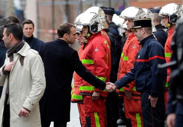 El Presidente de Francia, Emmanuel Macron, saluda a un bombero durante su recorrido por las calles parisinas, un día después de las manifestaciones de los