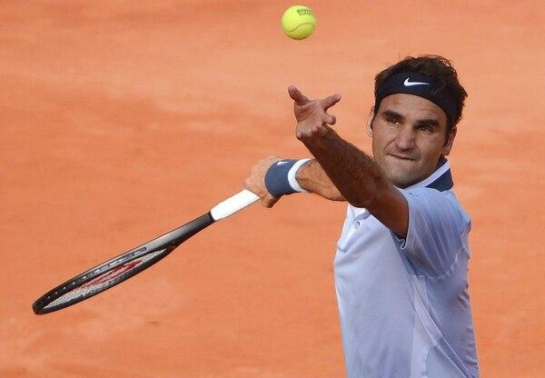 El tenista suizo Roger Federer saca ante el alemán Daniel Brands durante el partido correspondiente a la segunda ronda del torneo de Hamburgo, Alemania, hoy miércoles.