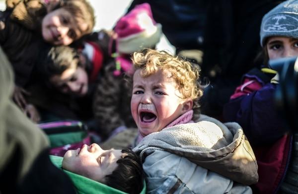 Un niño sirio llora mientras su familia y miles de sirios más esperan en el cruce fronterizo de Bab al Salam poder entrar a Turquía.