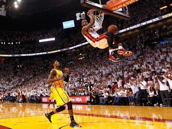 Dwayne Wade del Miami Heat cuelga del aro ante la mirada de Paul George de los Pacers de Indiana, ayer en el American Airlines Arena.   AFP