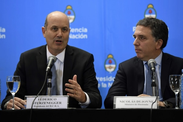 Argentina's Central Bank Governor Federico Sturzenegger (L) speaks next to Argentina's Finance Minister Nicolas Dujovne during a press conference in Buenos Aires, Argentina, on June 7, 2018. / AFP PHOTO / EITAN ABRAMOVICH