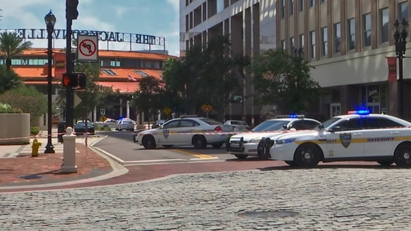 This handout image distributed courtesy of WJXT, a local Jacksonville television station, shows police cars blocking a street leading to the Jacksonville Landing area in downtown Jacksonville, Florida, August 26, 2018. - Several people have been killed in a mass shooting at a video game tournament in the northern Florida city of Jacksonville, local police said Sunday, August 26, 2018, adding that one suspect was dead. (Photo by HO / Courtesy of WJXT / AFP) / == RESTRICTED TO EDITORIAL USE / MANDATORY CREDIT: