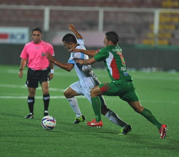 El jugador de Carmelita Ignacio Quesada (verde) marca al universitario Víctor Gutiérrez durante el juego de este miércoles.