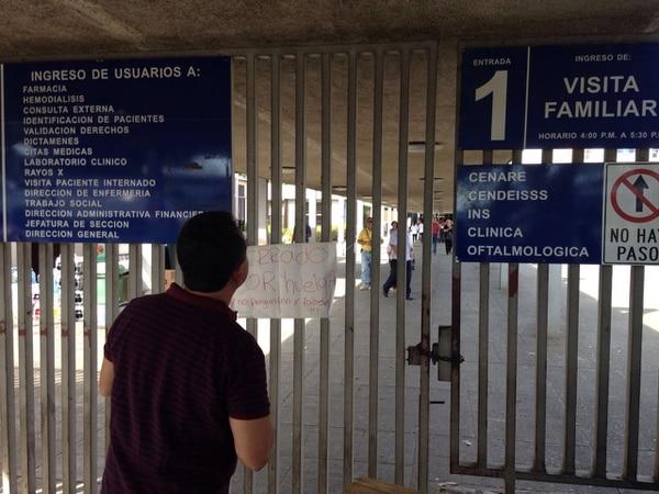 Un usuario lee uno de los rotulos ubicados en el hospital México y que impide el paso de los pacientes