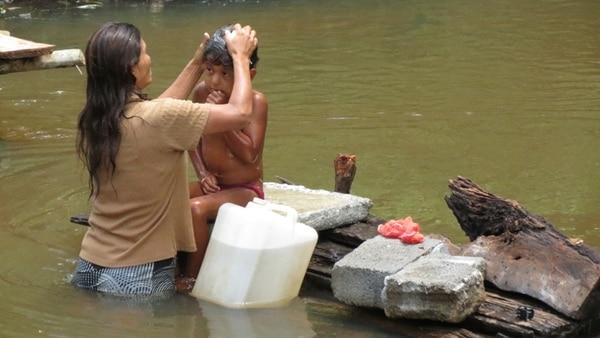 Emilia Carmona baña todos los días en el río a Carlos Hernández Betanco. La suya es una de las 80 familias de Isla Chica, en Los Chiles, sin servicio de agua potable. | CARLOS HERNÁNDEZ