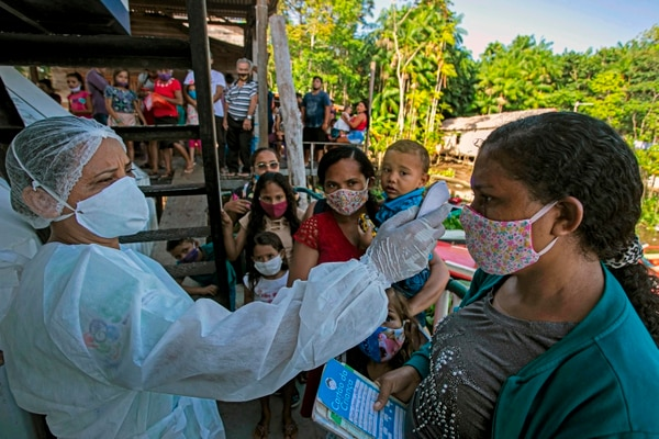 Un trabajador de la salud verifica la temperatura corporal de un paciente en la comunidad de Selma Barra, en el río Buissu, municipio de Melgaco en la isla de Marajo, estado de Pará, Brasil, el 30 de julio del 2020. Foto: AFP