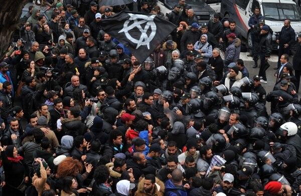 Manifestantes tunecinos se enfrentan a las fuerzas de seguridad que bloquean el acceso a las oficinas de la gobernación en Túnez durante una manifestación sobre alzas de precios y medidas de austeridad. AFP