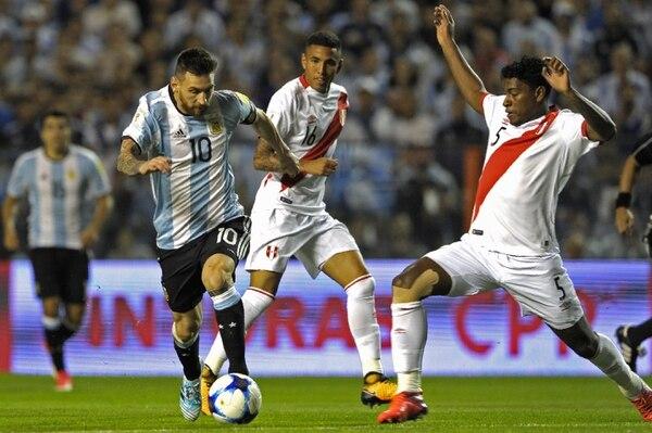 Lionel Messi (izquierda) supera la marca del peruano Miguel Araujo (derecha).