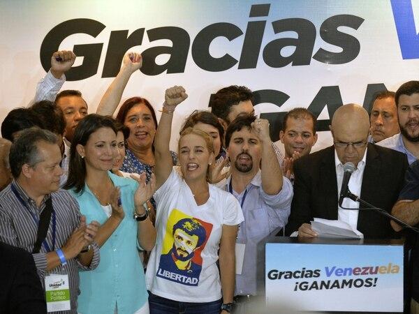 La esposa del encarcelado líder de la oposición venezolana Leopoldo López, Lilian Tintori (centro) junto a Freddy Guevara (segundo a la derecha) del partido Voluntad Popular, sonríe tras conocer los primeros resultados de las elecciones legislativas, en la sede del partido Movimiento de Unidad Democrática en Caracas, la mañana de este lunes.