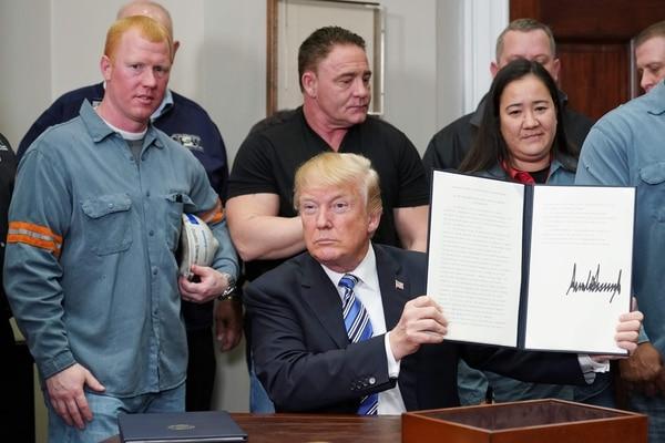El presidente de Estados Unidos, Donald Trump, mostró en la Casa Blanca la proclama donde se elevan los aranceles al acero y al aluminio. Estuvo en compañía de trabajadores de la industria de ese sector. Foto AFP / MANDEL NGAN
