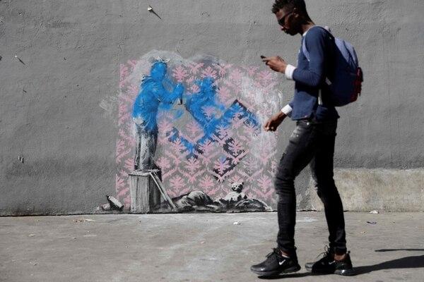 Esta obra de Bansky en el centro de refugiados del Ayuntamiento de París fue vandalizada. Foto: AFP/ Thomas Samson.