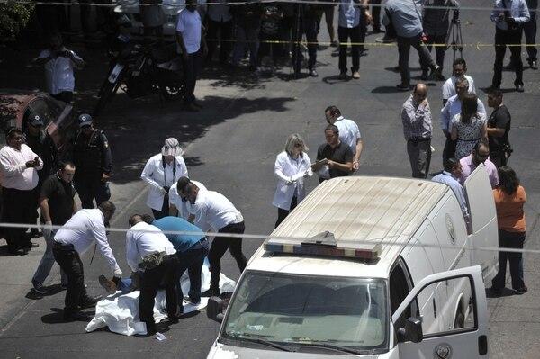 Investigadores y personal forense rodeaban el cuerpo del periodista Javeir Valdez, asesinado el lunes en una calle de Sinaloa, Culiacán.