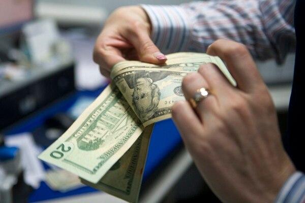 Un cajero contaba dólares la semana pasada. Actualmente, el Banco Central tiene suficientes para influir en el mercado. | ARCHIVO/LUIS NAVARRO.