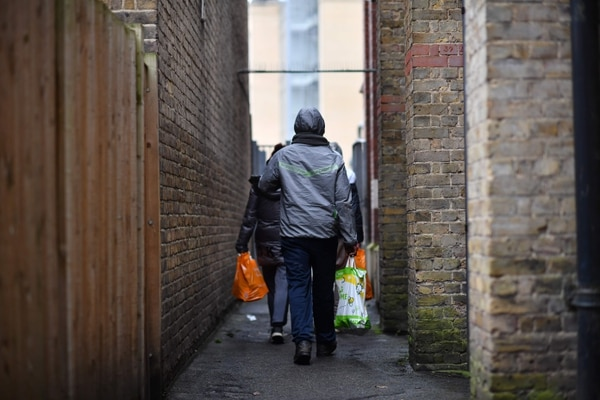 People leave with their food package after visiting the Slough Baptist Church food bank in Slough, west of London, on November 28, 2019. - As record numbers of Britons flock to food banks and homelessness soars, for many people rampant poverty, not Brexit, is the main issue in next week's general election. (Photo by BEN STANSALL / AFP) / TO GO WITH AFP STORY BY ROLAND JACKSON