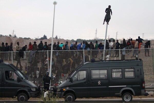 Inmigrantes se sentaron encima de una valla metálica que divide a Marruecos y el enclave español de Melilla este jueves.