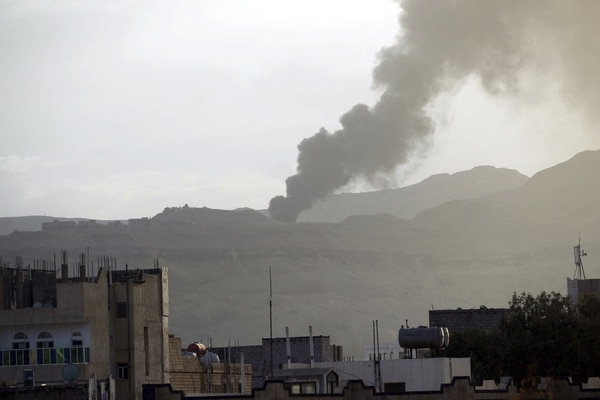 Vista de una columna de humo que sale de un almacén de armas que pertenece a la milicia chií de los hutíes tras un ataque aéreo efectuado por la coalición árabe en Saná, Yemen.