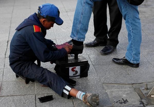 Este menor se gana la vida lustrando zapatos en las calles de la Paz.