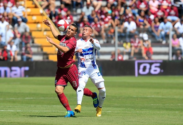 El morado David Guzmán peleó el balón con el brumoso Juan Gabriel Guzmán este domingo en el Ricardo Saprissa.