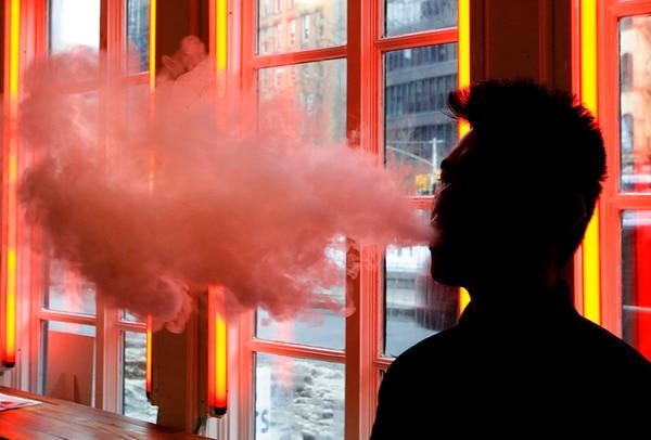 Un joven exhala el vapor de un cigarrillo electrónico en una tienda de Nueva York. (Foto AP / Frank Franklin II, Archivo)