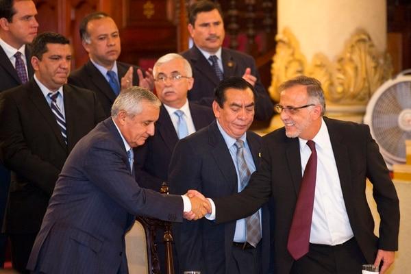 El presidente Otto Pérez Molina (izquierda), se saluda con el titular de la Cicig, Iván Velásquez, después de que el primer anunció que solicitará a la ONU que prorrogue el mandato de ese organismo. | AP