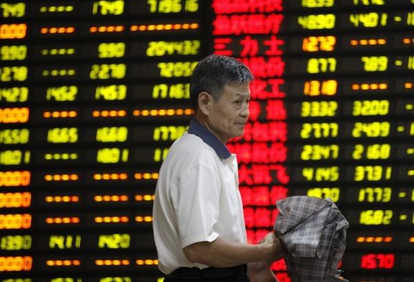 Un inversor pasa delante de una pantalla en una oficina en China. Las bolsas chinas sufrieron un fuerte desplome.   EFE