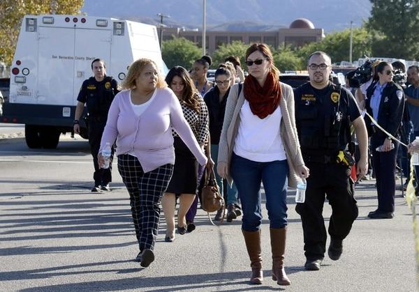 Un oficial de seguridad acompañaba el miércoles personas evacuadas de la escena del tiroteo en el Centro Regional Inland en la ciudad californiana de San Bernardino. | EFE