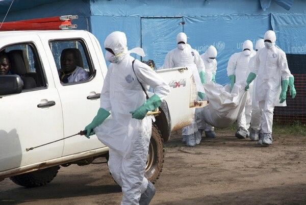 Trabajadores de la salud de Liberia llevan a enterrar a una mujer que murió a causa del virus del ébola, en el centro de aislamiento en Foya, condado de Lofa. El personal médico debe lidiar con el agotamiento, la escasez de personal y de suministros, más el temor real de contagio.   EFE