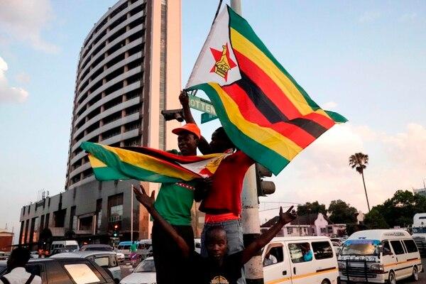 Decenas de personas celebran en la calle después de la renuncia del presidente de Zimbabue, Robert Mugabe, en la ciudad de Harare.