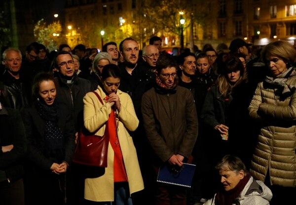 Las personas rezaban mientras la catedral de Notre Dame se quemaba en Paris, el 15 de abril del 2019. Foto: AP