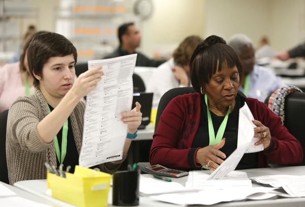 Personal temporal del Departamento de Elecciones en Renton, en el estado de Washington, abren y revisan votos que fueron enviados por correo al condado de King.